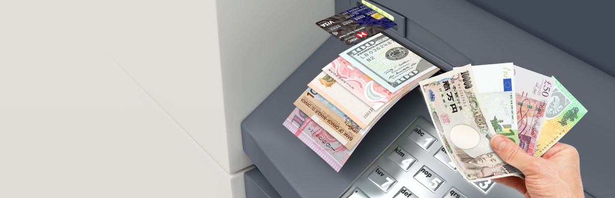 Withdrawing multiple currency banknotes from an ATM; imaged used for HSBC Everyday Global Visa Debit Card page.